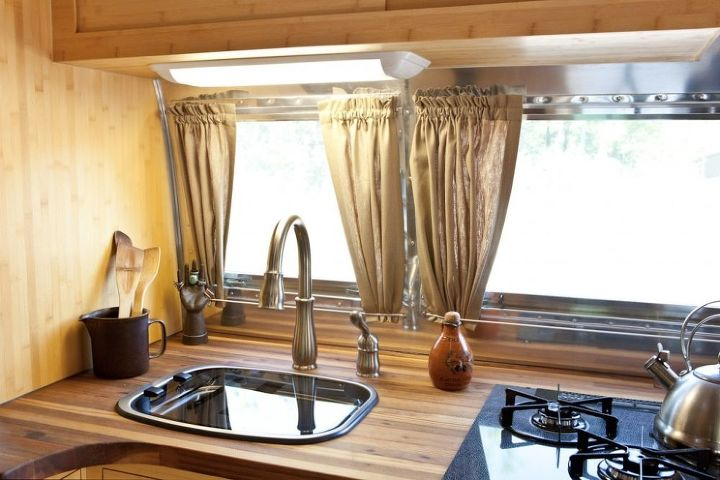 The kitchenette has a lift-up sink cover and a  stovetop with two propane and one electric burner.