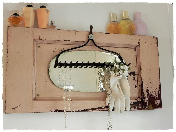 An old cupboard door with original paint, vintage mirror and rake mounted on top make an interesting focal point.