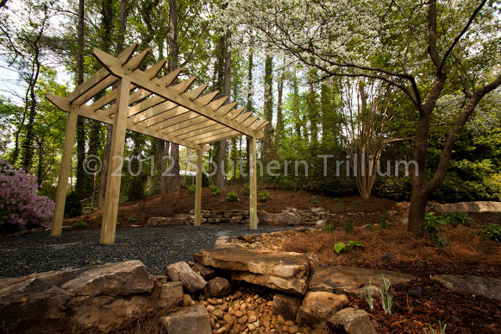here is what you can do with a mostly shady backyard get rid of the grass and make, flowers, gardening, landscape, outdoor living, patio, perennial, Looking up at the pergola we built for the client You can see the solid stone bridge set over the dry streambed