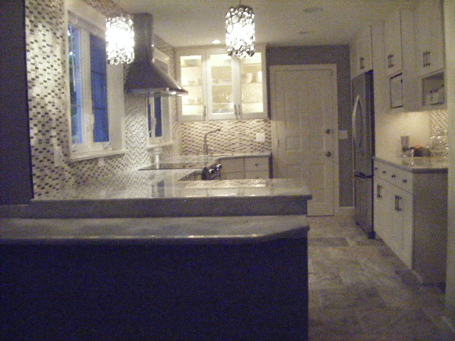 Finished.  Travertine marble floor, and travertine and glass backsplash.  Counters are cararra marble.