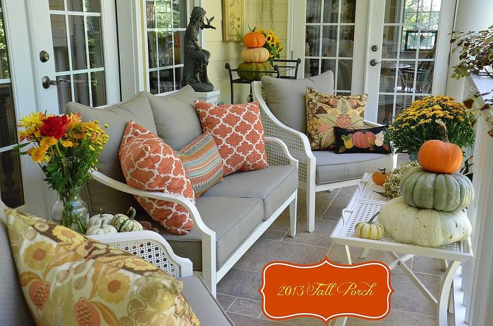 Porch decorated for Fall with natural elements, and specialty pumpkins, pillows in shades of rust, blues, and browns, mums, and flowers.