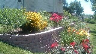 q cheapest way to make a large retaining wall, concrete masonry, landscape, outdoor living, This is one section everything is grown up a lot since this pic
