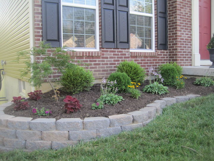 Retaining wall built with pavers.  The basic steps were to dig out the area & add some sand to level the blocks.  Once they were all in place, he added tiny pea gravel to help with drainage & then filled it with topsoil until it was level with the rest of the ground.