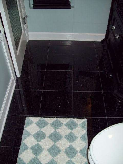 Here is the new blue butterfly black granite tile floor with black grout.  Added arctic white baseboard and trim to complete the look.