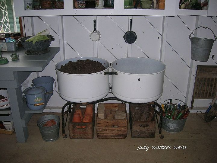 Old double porcelain laundry tubs make great containers for potting soil. The sm. enamelware pans hanging on the wall are used to scoop out the  soil.