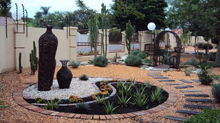 does anyone have any idea what we can do with is front yard nightmare, gardening, landscape, A Yin Yan sign with focal pots or plants would give the space an interesting lift This project was done in 2009 This is your typical hard Landscaping based on a dry riverbed not seen on this specific picture