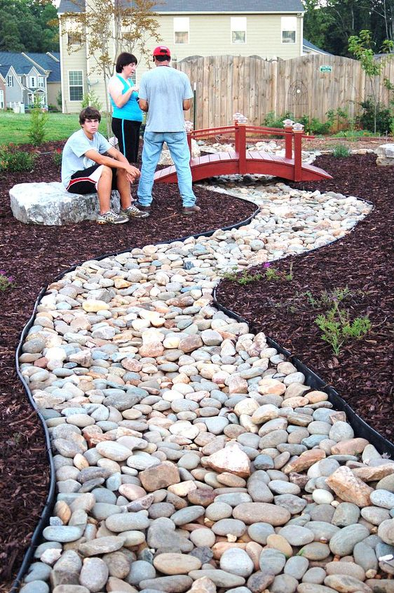 Rain water run off problem solved with a gorgeous dry creek bed, Japanese bridge.