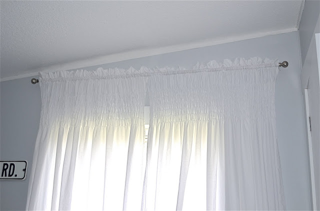 I made the curtains out of bed sheets from Walmart and elastic thread.