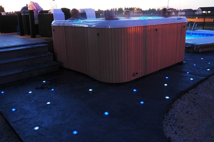 "10 White and 12 Blue Skyfuel 2"" diameter round solar LED landscape lights installed in concrete around a hot tub spa. Install these yourself in minutes with some common household tools."