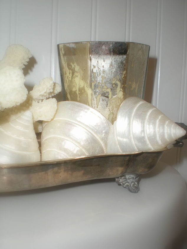 Shells, coral, and a mercury glass candle are corralled in a vintage silver plate tray on the back of the commode to break up the vast expanse of white and add a little more style to such a tiny space.