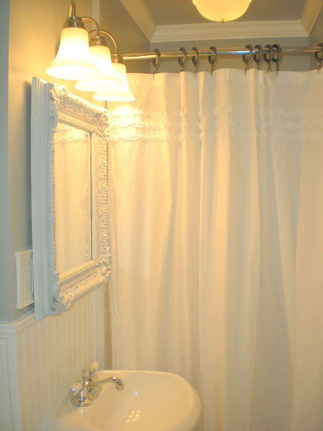 A tuxedo ruffled Rachael Ashwell shower curtain from Target helps soften the edges of this nearly monochromatic space.