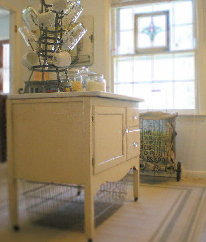 An antique Hoosier cabinet base makes a kitchen island. A rather large wire basket serves as additional storage.