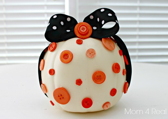 White pumpkin decorated with buttons and ribbon.