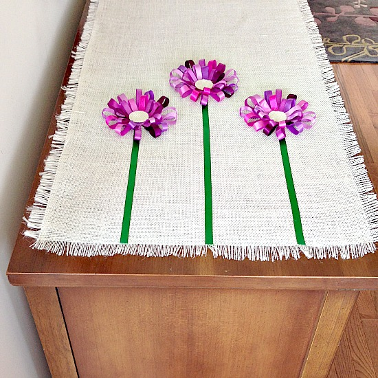 Attach the stems starting at the fringe using fabric glue for a smooth fit and next glue the blooms for a finish look.