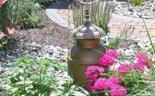 how to camouflage an ugly well pipe, landscape, fire pit, How do you camouflage an ugly well pipe Cut out the bottom of an old milk can and place it over top Easy