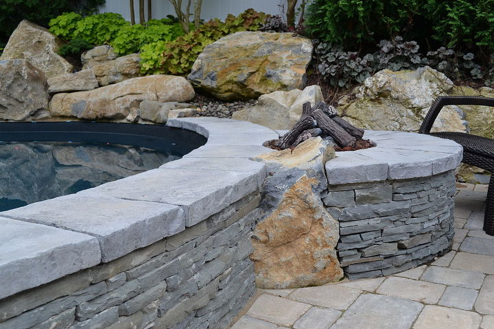 Gas fire pit integrated into the pool wall, using stacked bluestone and moss rock boulders