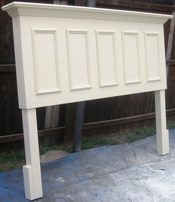 King size door headboard made from and old door - panels on the front, side skirts, crown molding supported shelf and legs added.  Finished in a satin Popcorn white.