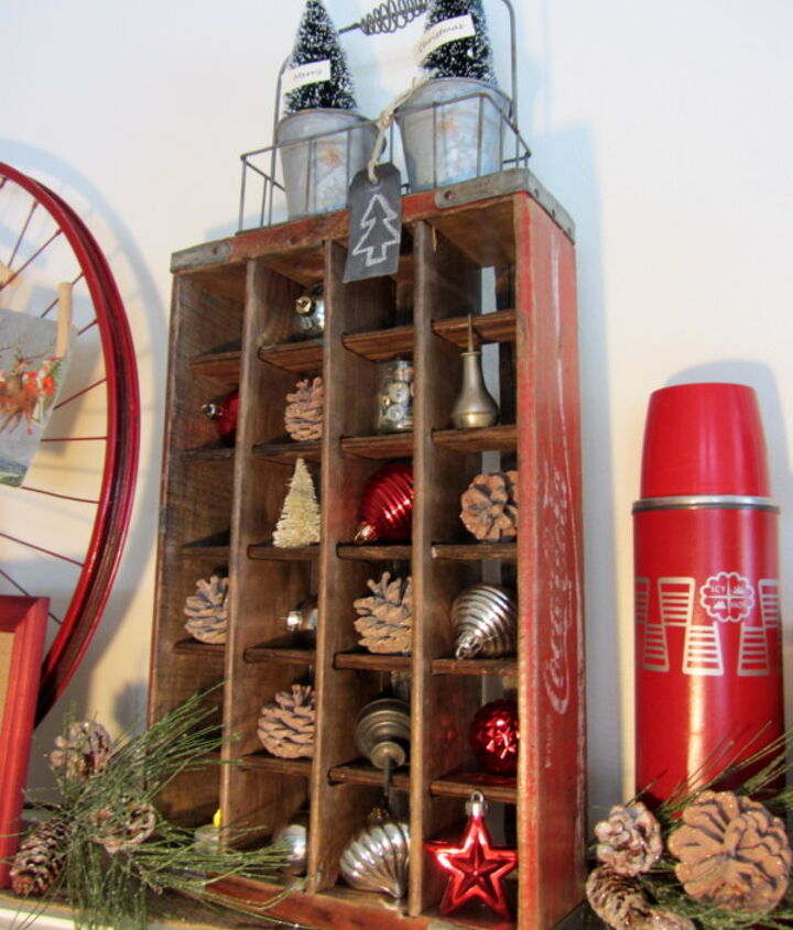 Vintage Coca-cola crate with pine cones, ornaments, oil cans, and buttons.