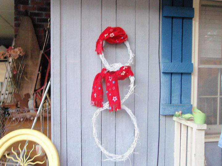 Snowman grapevine wreath that is dressed for cold weather.