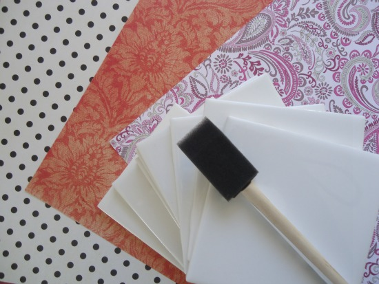 You will need ceramic tiles, scrapbook paper, Mod Podge, and a spray acrylic sealer