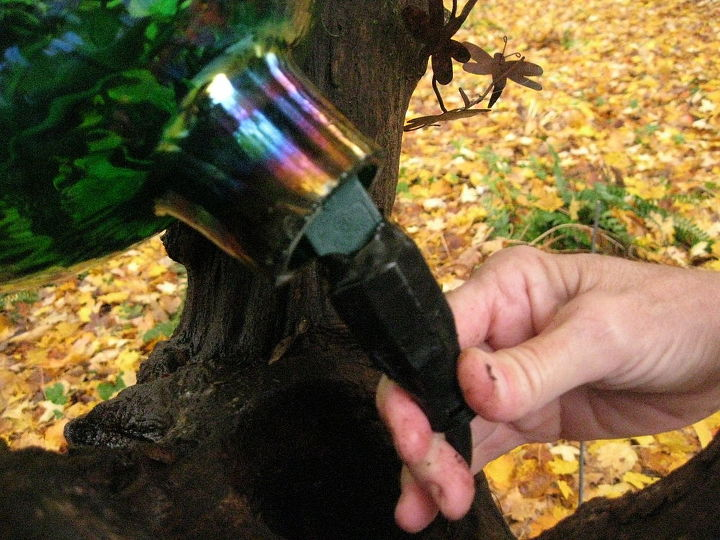 I tape the extension cord and the end of the strand of lights together with electrical tape so they cannot fall back through that long hole in the log! Helps keep any moisture out too.