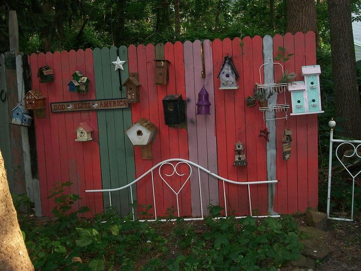 back yard fence, fences, outdoor living, pets animals, I used all of my left over paint to paint the fence added an old bed frame I found on the side of the road and birdhouses most hand painted