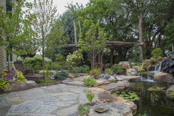 A rustic pergola created with trees and branches adds to the natural feel of this revamped landscape.