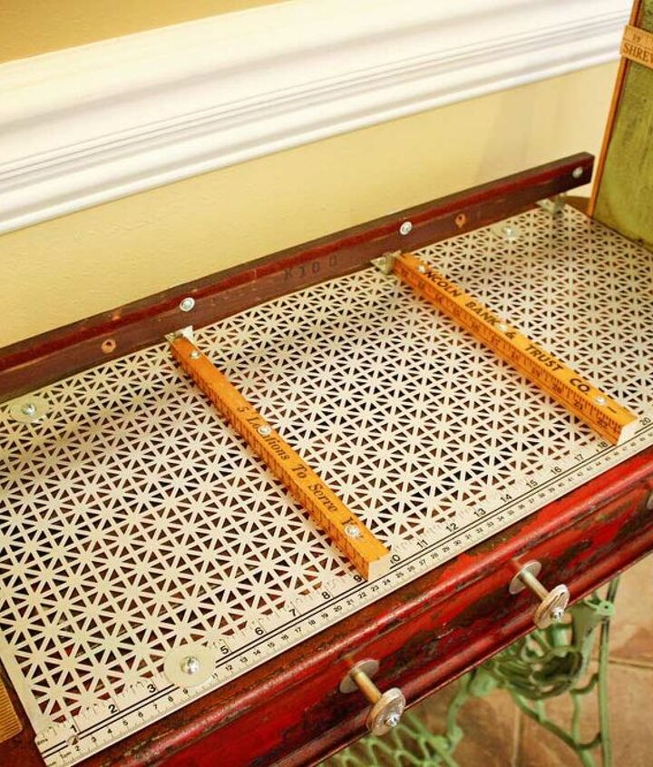 I used a found metal screen for the gym baskets to slide and rest on.  Some old measuring sticks are used for guides and a vintage part from a piano is used as a back bumper.  Repurposed Red Wagon Sewing Machine Base Storage Table by G