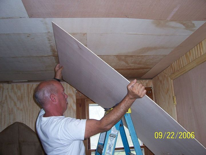 Handyman installing lauan boards over existing ceiling.