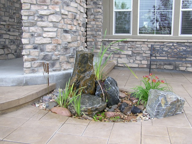 A pouting rock at this homeowner's front door adds interest and the sound of water.