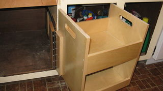 q any ideas for replacing our vinyl laminate contractor grade kitchen, flooring, kitchen design, tile flooring, Here you can see how they built this pull out box on a piano hinge and it has 2 storage sections There is a huge cavity inside this cabinet that they got in there built two 2 huge flat trays to pull over to the pullout