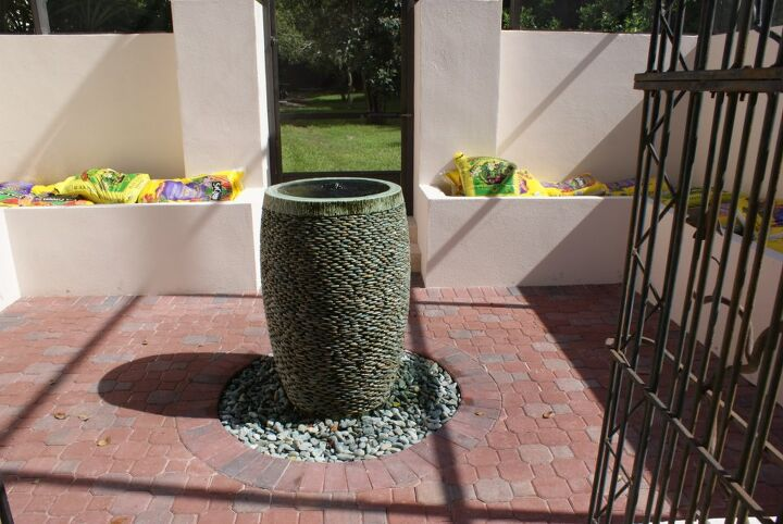 new pictures, gardening, Courtyard bubble fountain we are using herbs giant Iris and Hawaiian ties in raised planters