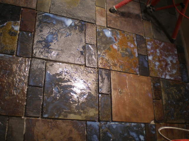 infloor heating under the slate, the milky substance is a gloss sealer.