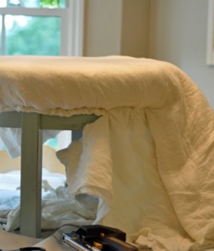 I painted the legs and sides of the table my favorite color blue and distressed it just a little using sand paper ...Four layers of quilt batting insured a cushy feel! I used an electric stapler which was a necessity for this project!