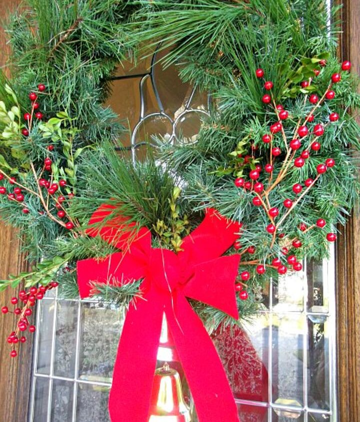 A flimsy, faux wreath is brought to life with lots of fluffing and tufts of fresh boxwood and pine boughs.