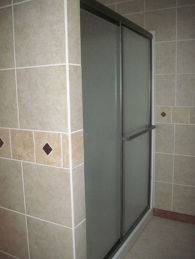 The only thing we kept from the original bathroom was the shower.  It was spray painted in a rubbed bronze to match the the rest of the bathroom.  We also sprayed the heat vent, garbage can and the door knob in the same paint.