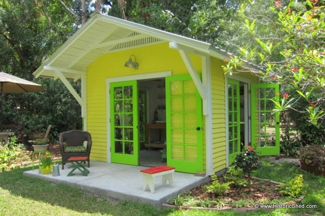 The shed has 3 sets of French doors and a 4' roof overhang supported by large brackets.
