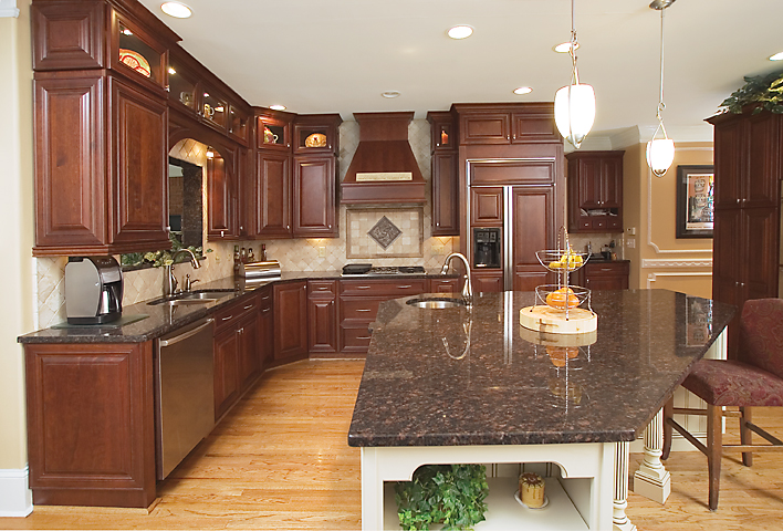 The main kitchen is traditional in style with a custom island to accent the rich woods. The granite is Tan Brown.