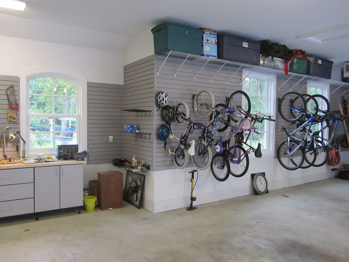 Bikes are hung with slatwall bicycle hooks and storage containers rest on shelves high above.