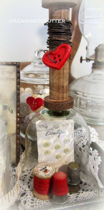 I removed the measuring tape and added a vintage button card, thimbles and red thread under the re-purposed votive shade/cloche.
