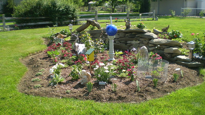 flower beds, flowers, gardening, I wanted a mound in the yard The neighbors were taking grass out so we had it put in our yard I cleaned it up and dug flower bed in front and one in next picture Used grass for instsnt grass on top of mound rock in front