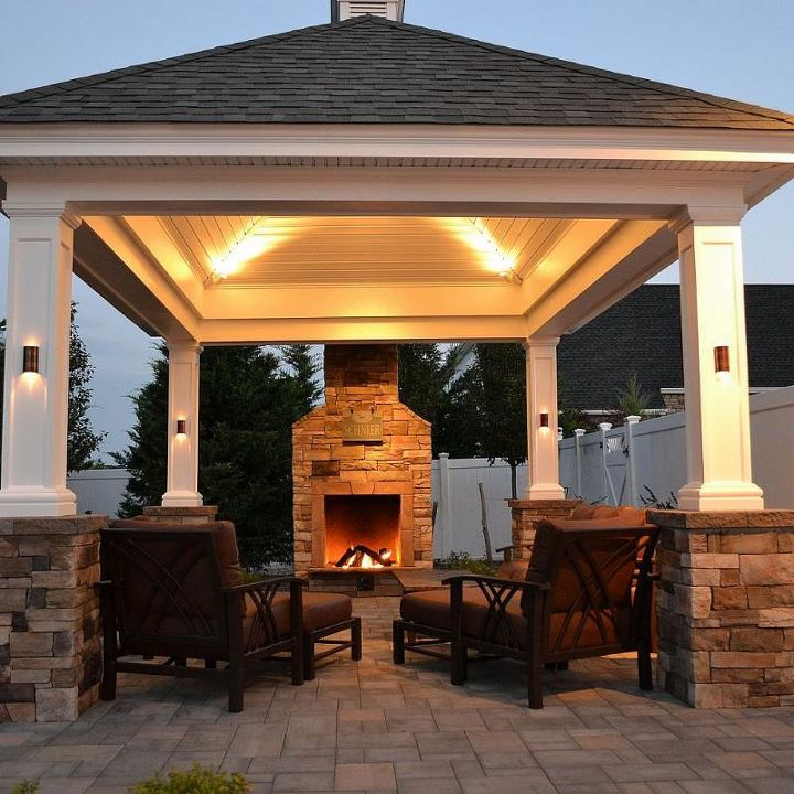 can a lovely backyard retreat be budget friendly, curb appeal, fireplaces mantels, landscape, outdoor furniture, outdoor living, At the edge of a patio beside a lovely shingle roof gazebo pergola this fireplace not only offers warmth in autumn and winter months but it creates the perfect ambience for conversation