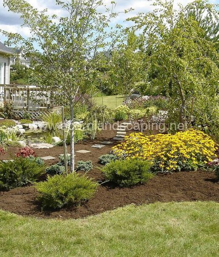 Backyard Landscape Design for this property located in Henrietta NY included removing a large boulder from the existing retaining wall and having the waterfall and stream start here. We also added an koi fish pond and lots of plants.