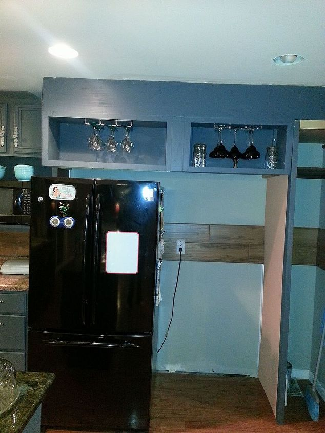 The cabinets are built out above the refrigerator and soon to be new freezer. I built the frame so the cabinets hang from the ceiling and I can reach them above the frig. A broom closet and catch all is the right