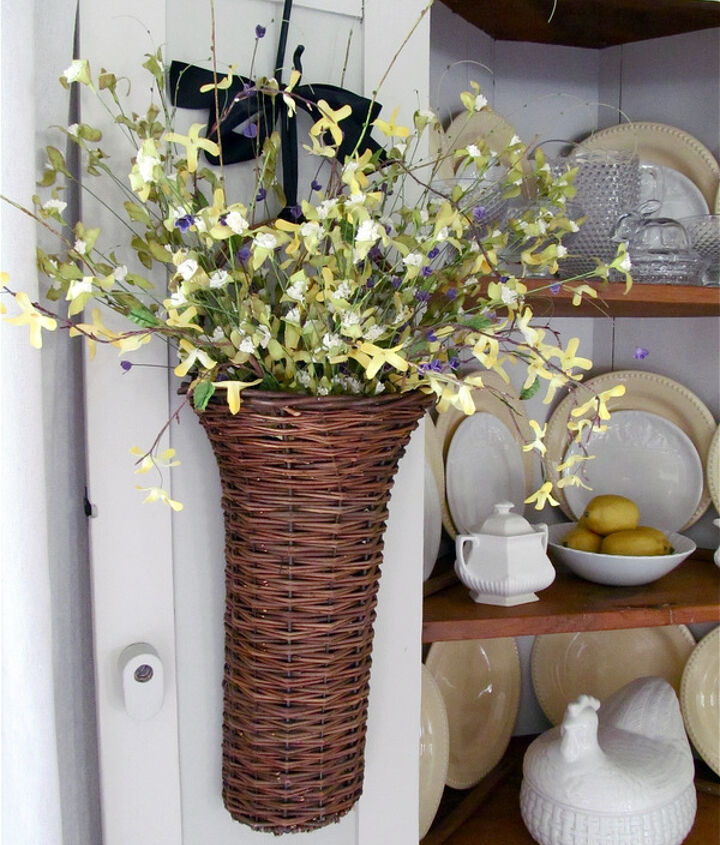 Basket of faux forsythia and wildflowers hanging on the door.