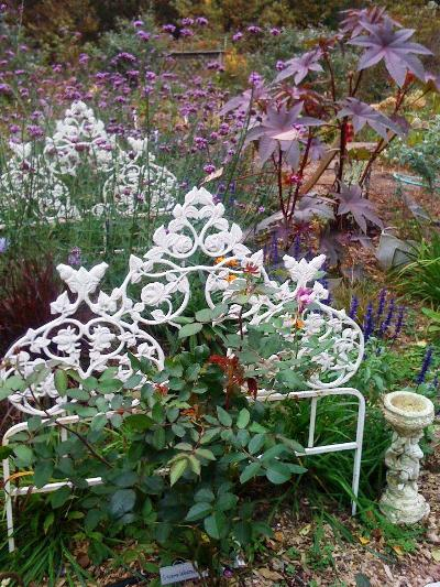 "Audrey Osborn says, "" This is my ""bedroom garden,"" a white iron bed,  filled with flowers. The Copper castor bean plant is watching over the area ."""