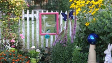 Large flower etched etched in white on garden mirror as if it were a flower itself growing in the garden.