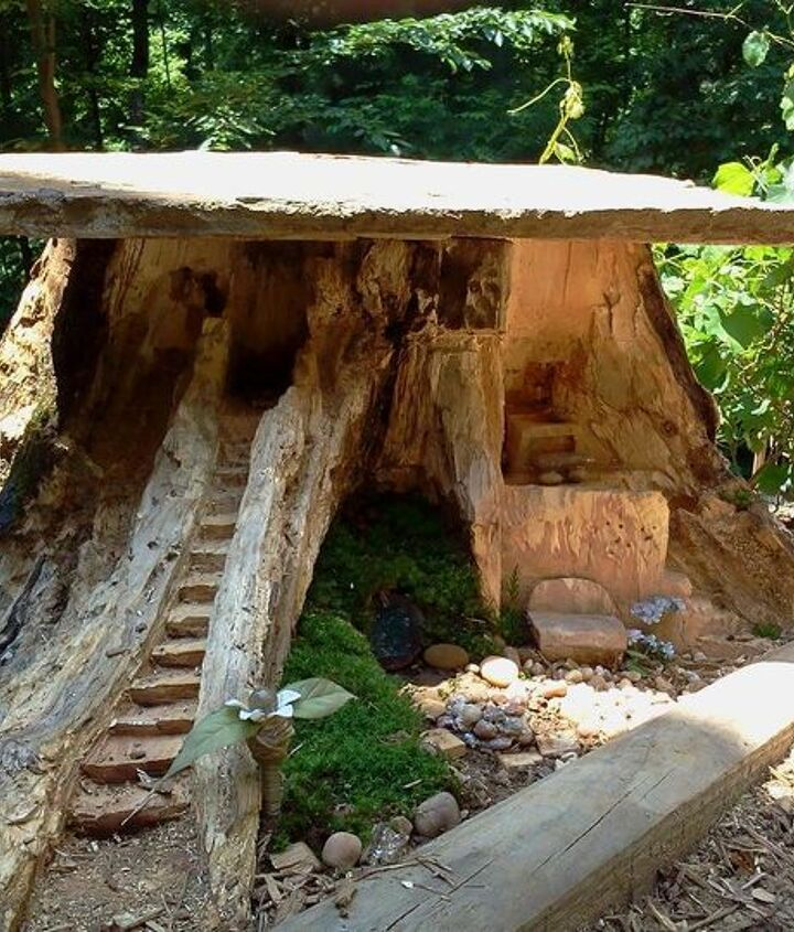 making a fairy home from an old stump, gardening, outdoor living, A little more added on the door is temporary until I find or make a round hobbit door It s a campfire and a bar above the bench I have a hole where a slide will go to ride into the lake I will create on the next bend