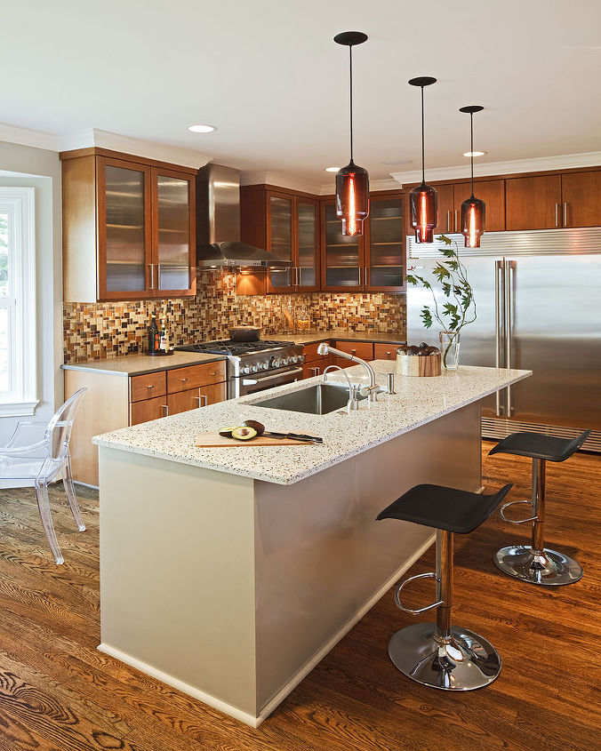 """Eco-friendly countertop materials and a recycled glass title backsplash in the kitchen suited the client's desire for a """"transitional style"""" interior to blend with their traditional home."""