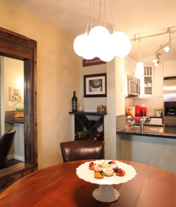 A contemporary light fixture and new dining table pair well with the mirror the client had picked up at an Estate sale several years prior